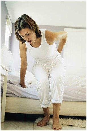 женщина встает с постели с болью