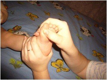 Родитель массажирует руками стопу малыша