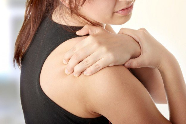 девушкаиспытываетболь в плече