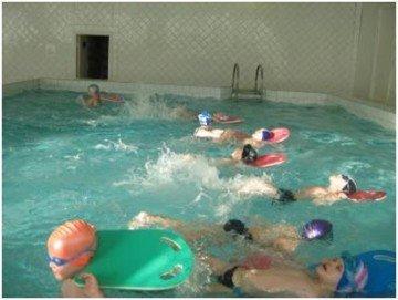 Дети плавают в бассейне на досках