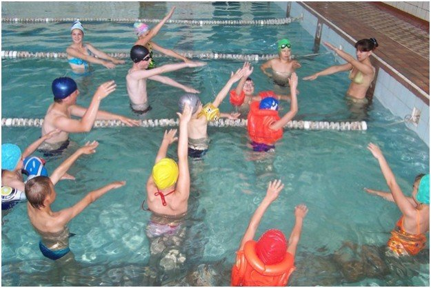 дети делают упражнения в воде под наблюдением учителя