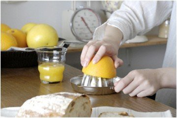 человек выжимает сок апельсина
