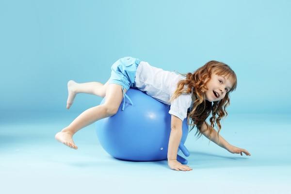 Девочка лежит на фитболе